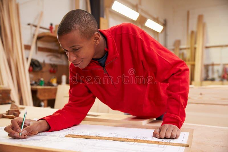 Lehrling, der mit Plänen in der Zimmerei-Werkstatt arbeitet stockfotos