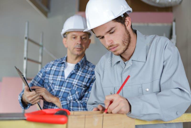 Lehrling, der mit Plänen in der Zimmerei-Werkstatt arbeitet lizenzfreies stockbild