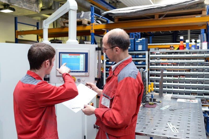 Lehrling und Trainer in einer Metallarbeitsfirma - apprenticeshi lizenzfreies stockbild