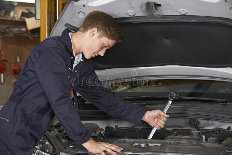 Lehrlings-Mechaniker In Auto Shop, das an Automotor arbeitet lizenzfreies stockfoto