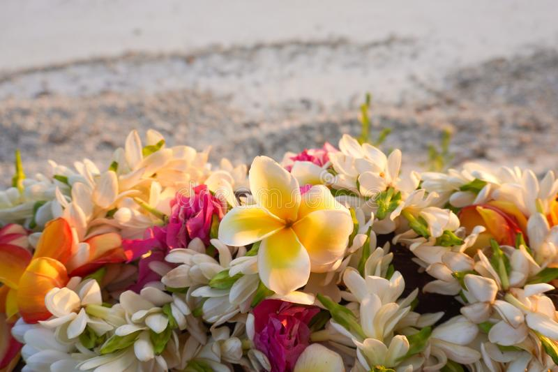 A lei of beautiful tropical flowers rests on a railing above a white sandy beach. With copy space stock photos