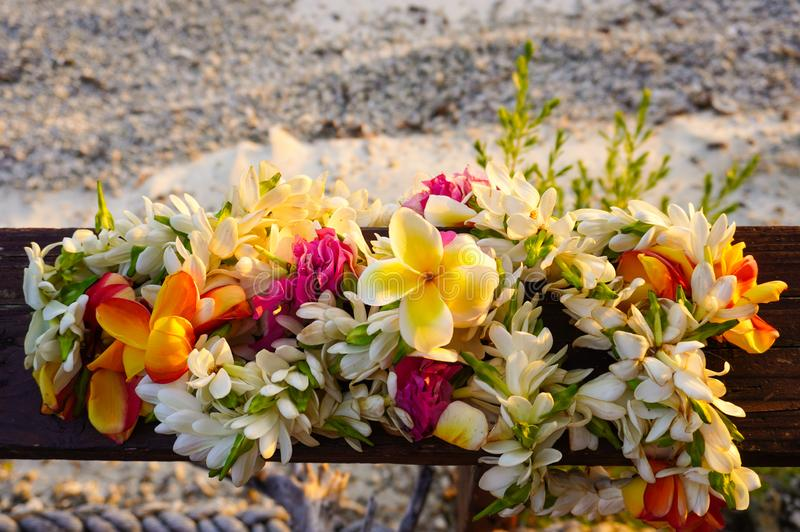 A lei of beautiful tropical flowers rests on a wooden railing above a white sandy beach. With room for copy space stock photo