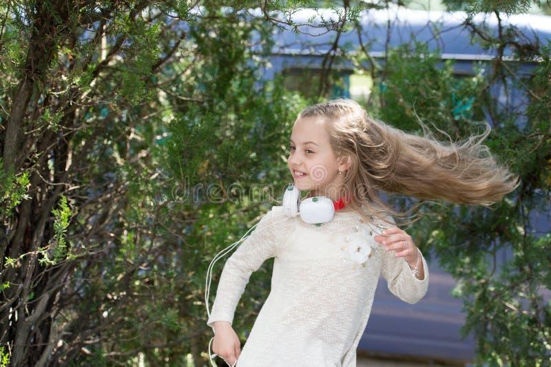 Lei che irradia energia Il bambino della ragazza ascolta cuffie di musica Il bambino ascolta canzone e ballo Lista musicale radio fotografia stock libera da diritti