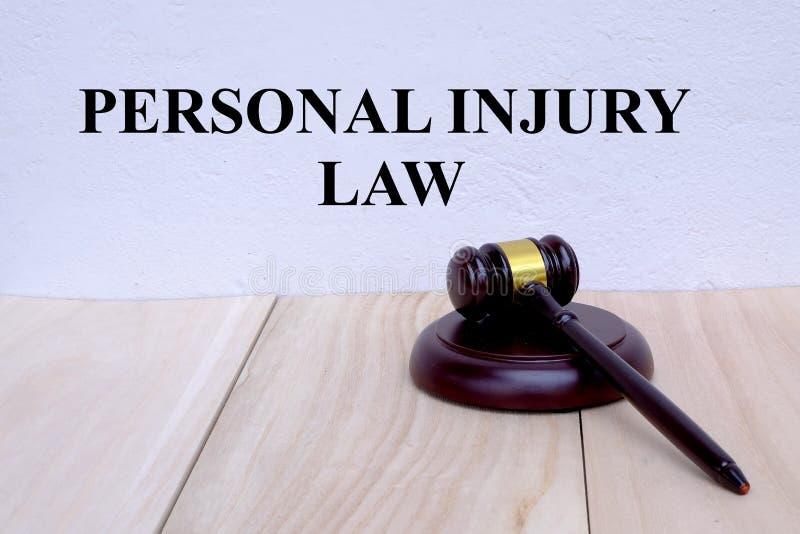 Lei dos ferimentos pessoais escrita na parede com o martelo no fundo de madeira Conceito da LEI imagem de stock royalty free