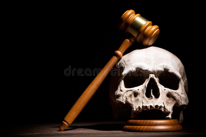 Lei, justi?a e conceito legais do murderment Martelo de madeira do martelo do juiz no cr?nio humano contra o fundo preto Espa?o l foto de stock royalty free