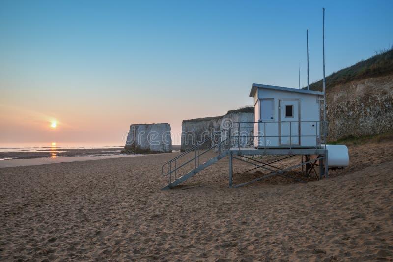 Leibwächterhütte auf leerem Strand während des bunten Sonnenaufgangs mit Felsen c stockfotografie