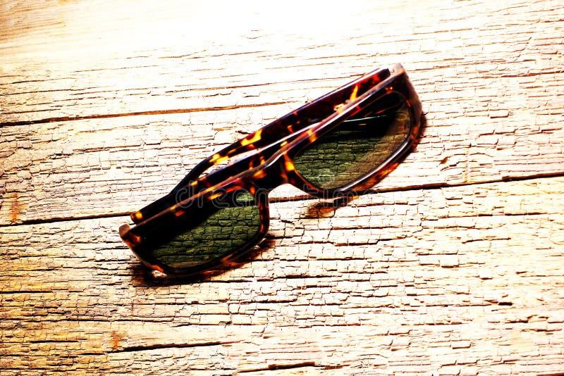Leicht-schützende Gläser auf der strukturierten Oberfläche des alten Holztischs lizenzfreie stockfotos