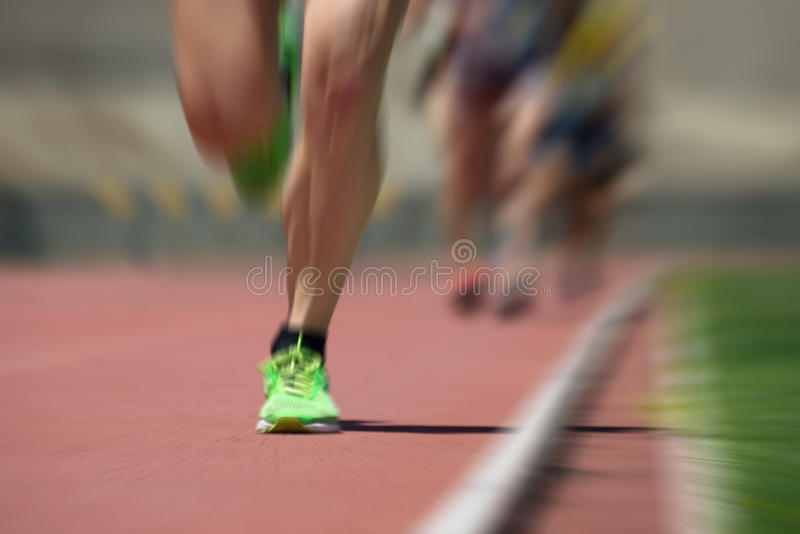 Leichtathletikleute, die auf dem Bahnfeld laufen stockbild