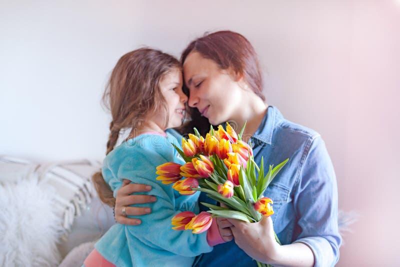 Leichte Umarmungsmütter und -töchter, Glückwünsche am Feiertag und Blumen Mutter ` s Tagesgru?kartenkonzept Ein Blumenstrauß von  stockbild