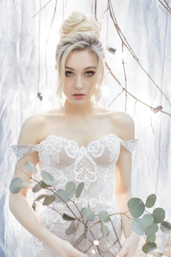 Leichtes Porträt einer schönen netten glücklichen Braut mit einem festlichen hellen Make-up der schönen Frisur in einem Hochzeits stockfoto