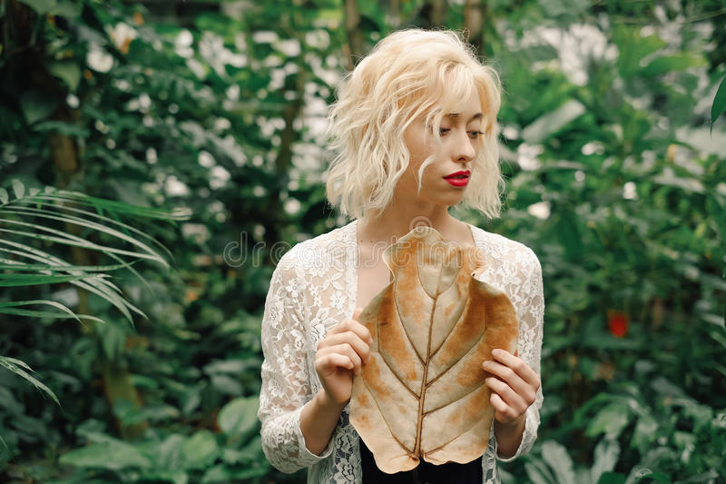 Leichtes Porträt von Blondinen im tropischen botanischen Garten lizenzfreie stockfotos