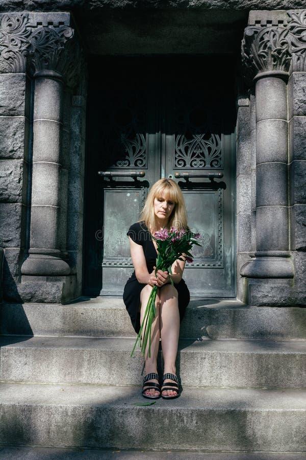 Leid: Frau, die auf Mausoleums-Schritten sitzt stockfoto