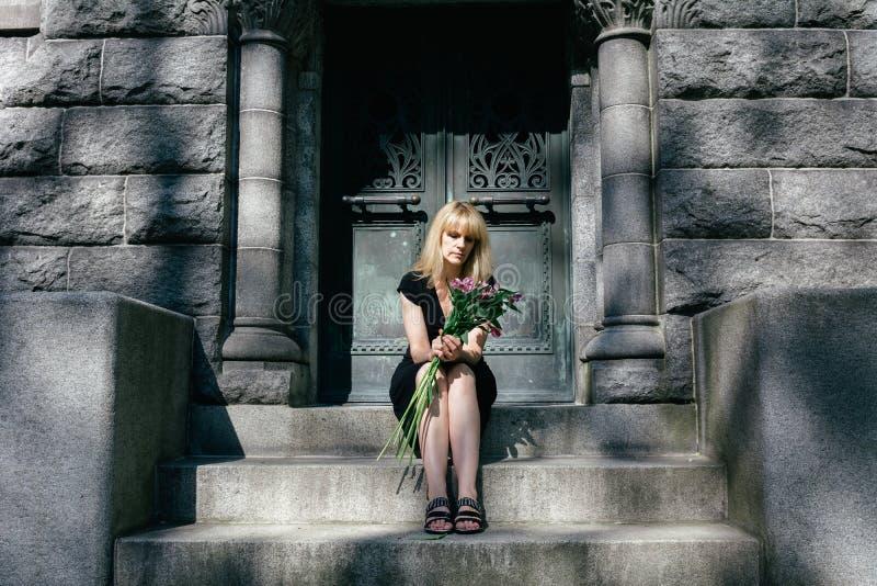 Leid: Frau, die auf Mausoleums-Schritten sitzt stockfotografie