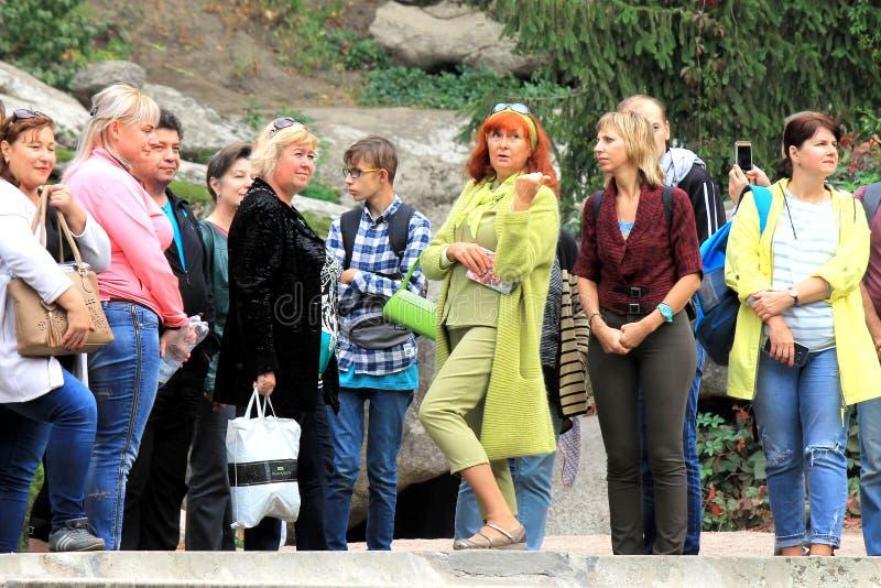 Leiden de bejaarden met rood haar en de groene kleren reizen Sophia Park in Uman, de Oekraïne stock afbeeldingen