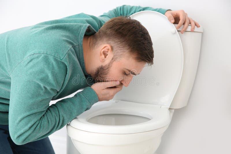 Leiden des jungen Mannes von der Übelkeit über Toilettenschüssel lizenzfreies stockfoto