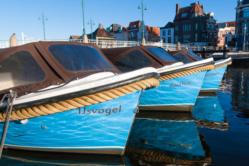 Motor boats docked in a canal of Leiden in the Netherlands stock images