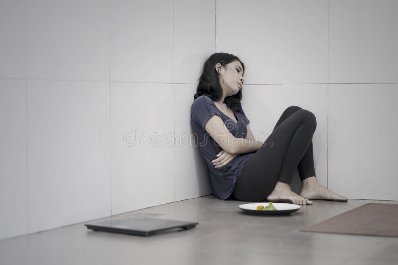 Leidende Magersucht der jungen Frau am Badezimmer lizenzfreie stockfotos