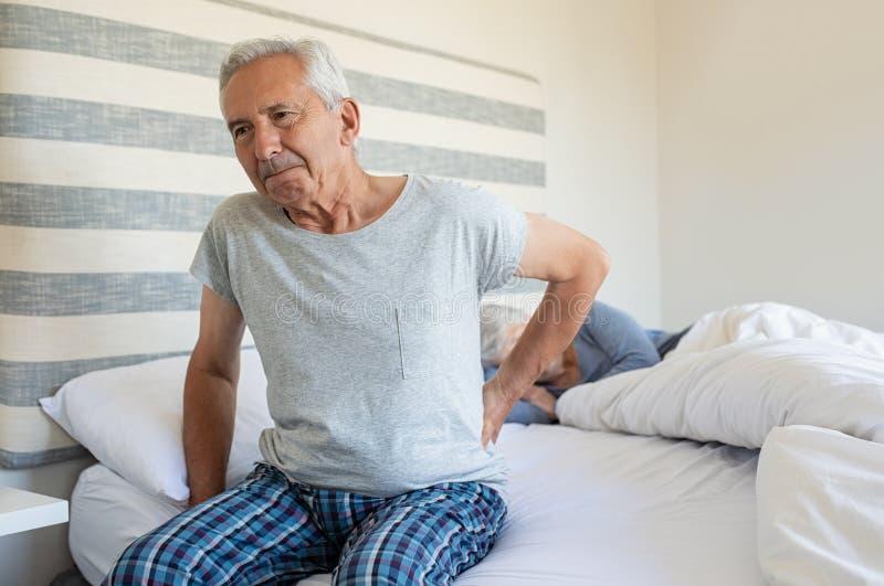 Leidende Rückenschmerzen des alten Mannes stockbild