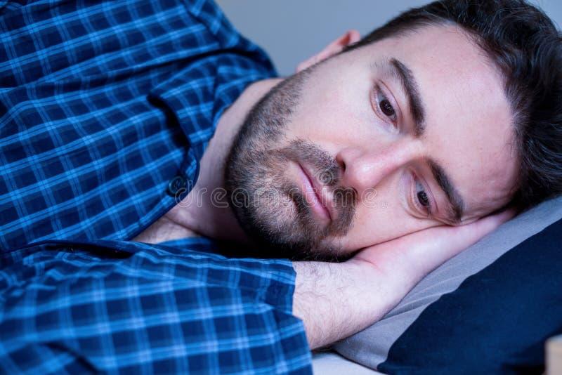 Leidende Schlaflosigkeit des Mannporträts, die versucht zu schlafen lizenzfreie stockbilder