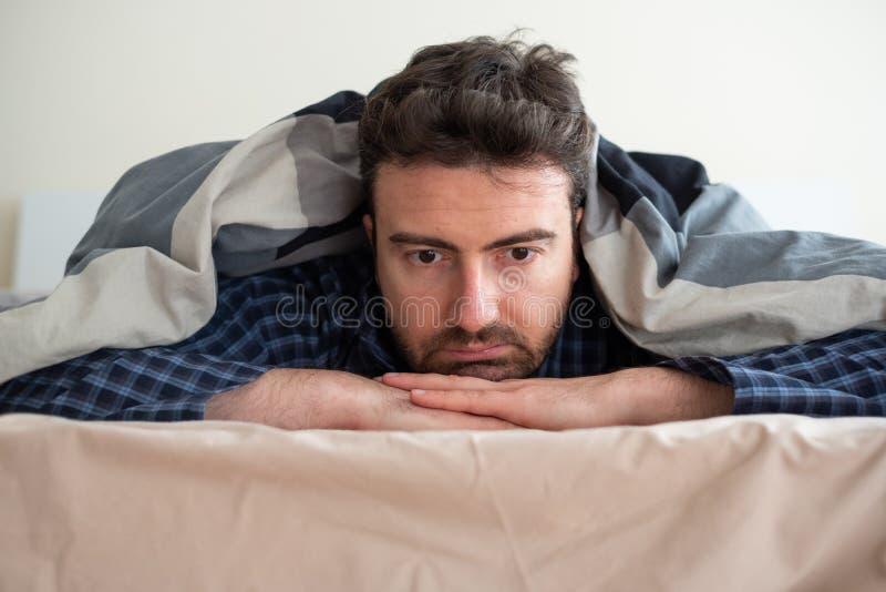 Leidende Schlaflosigkeit des Mannporträts, die versucht zu schlafen lizenzfreie stockfotos
