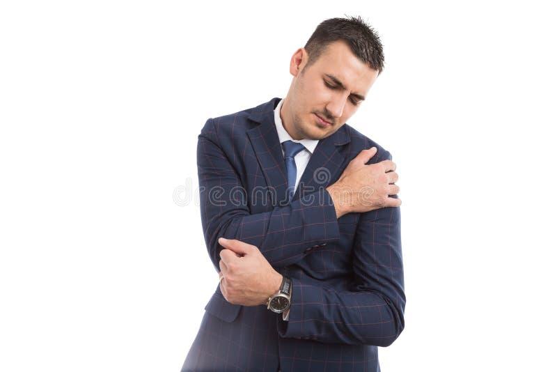 Leidende Schulterschmerz des jungen Geschäftsmannes stockfoto