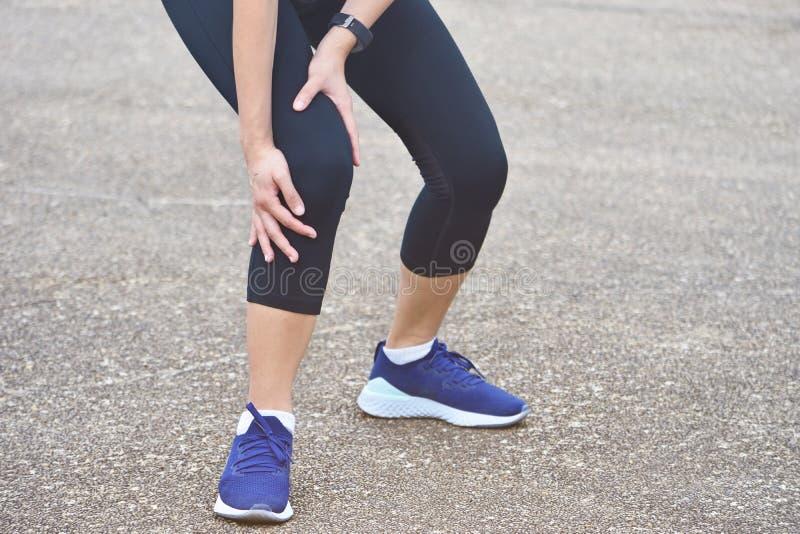 Leidender junger Läufer mit Beinverletzungsstand auf Boden lizenzfreie stockfotos