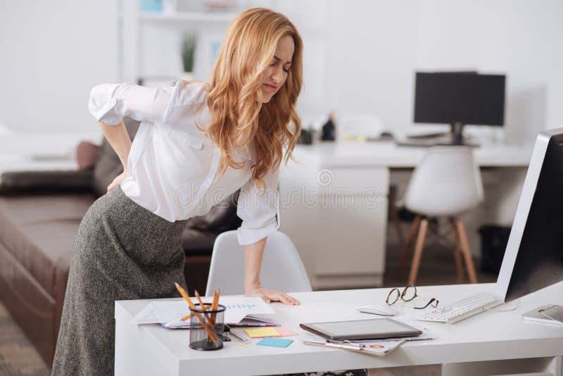 Leidender junger Sekretär, der im Büro schlecht sich fühlt lizenzfreies stockbild