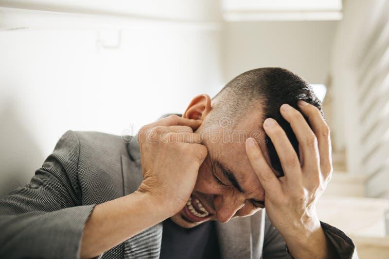Leidender Mann mit seinen Händen in seinem Kopf stockfoto