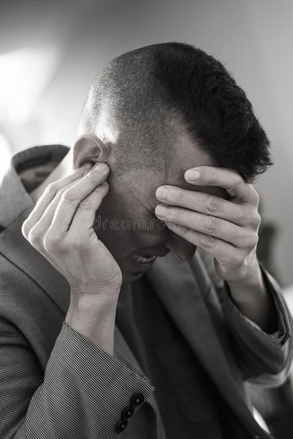 Leidender Mann mit seinen Händen in seinem Kopf stockbild