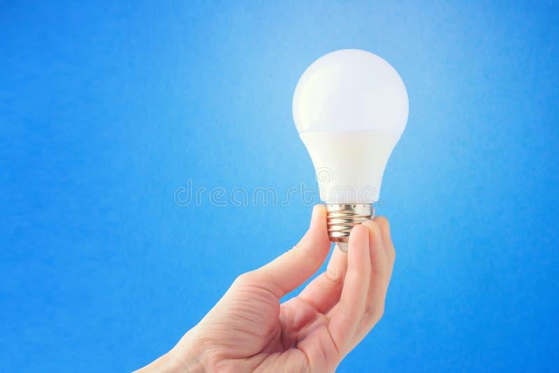 LEIDENE lamp ter beschikking op een blauwe achtergrond Concept het idee stock afbeelding