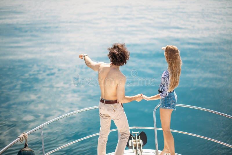 Leidenschaftliche Liebhaber, die auf Bogen der Plattform beim Segeln auf Yacht tanzen stockfoto