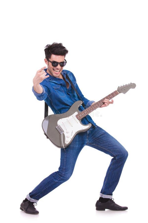 Leidenschaftlicher Gitarrist, der ein Rock-and-Rollhandzeichen macht lizenzfreie stockfotos