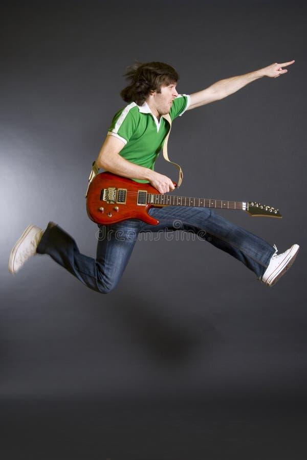 Leidenschaftlicher Gitarrist springt in die Luft lizenzfreie stockfotografie