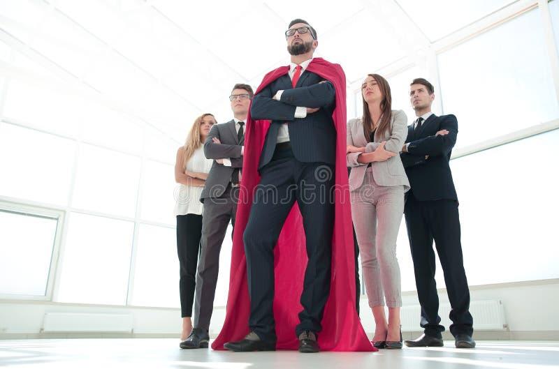 Leider in de rode mantel en het commerciële team die zich verenigen stock afbeeldingen