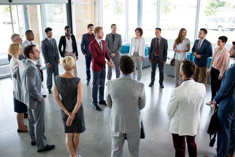 Leider die zich in cirkel van zijn succesvol commercieel team bevinden stock foto
