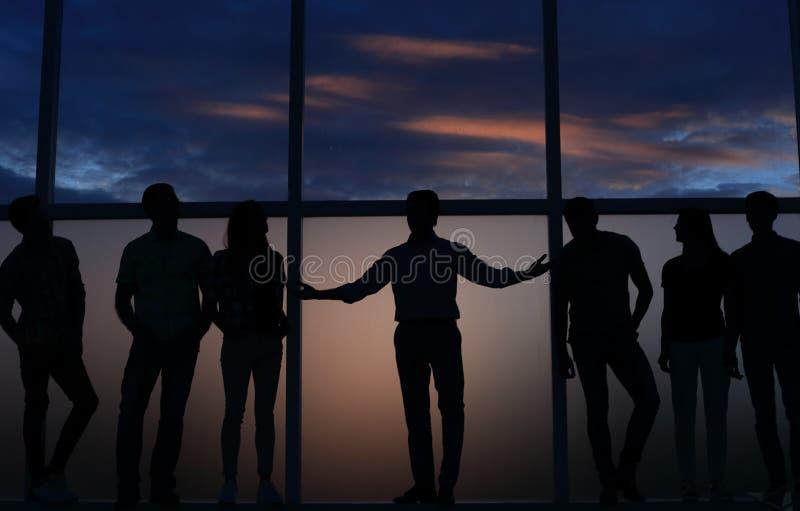 Leider en een groep jongeren die zich dichtbij een groot venster bevinden royalty-vrije stock fotografie