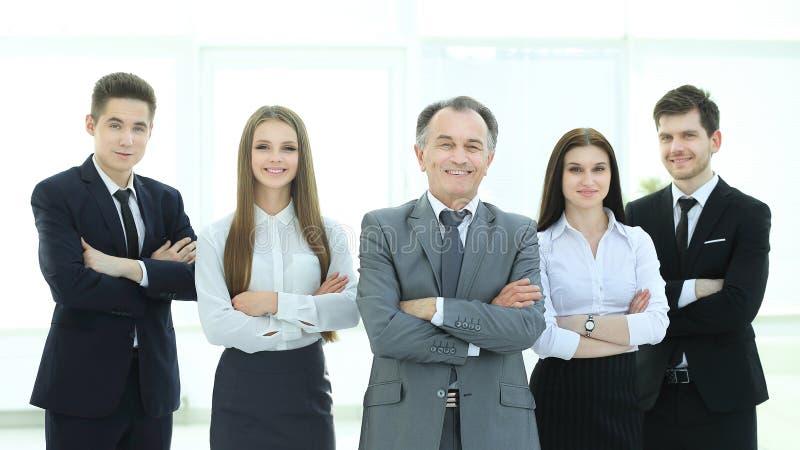 Leider en een zeker commercieel team op de achtergrond van het bureau stock afbeelding