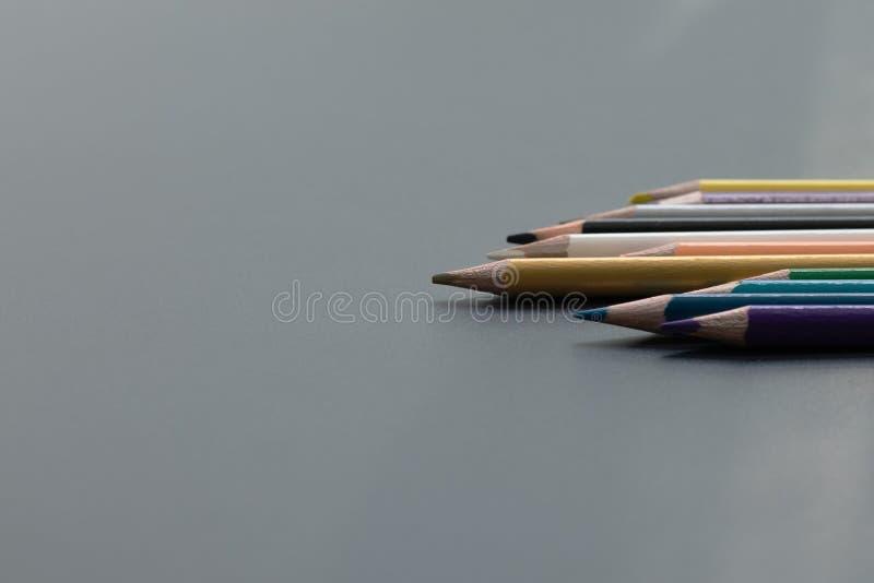 Leidings bedrijfsconcept Het gouden kleurenpotlood leidt andere kleur op zwarte achtergrond stock afbeeldingen