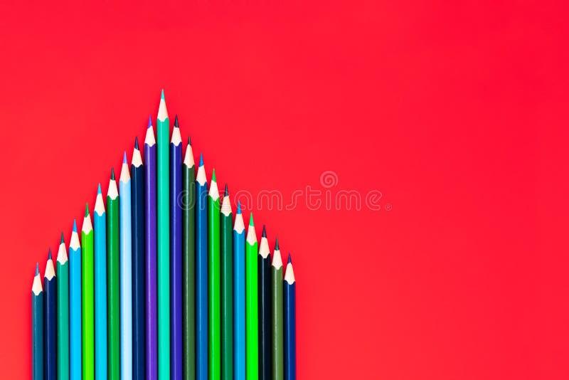 Leidings bedrijfsconcept het groene kleurenpotlood leidt andere kleur op rode achtergrond stock afbeeldingen