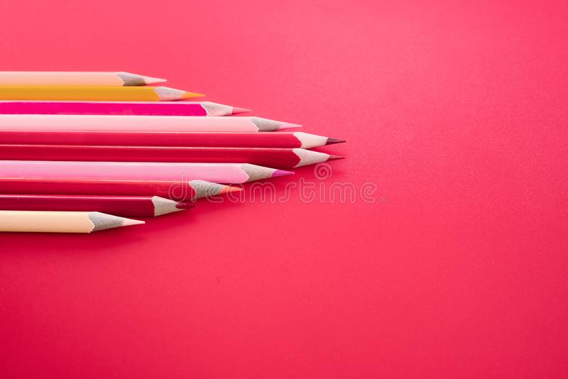 Leidings bedrijfsconcept het rode kleurenpotlood leidt andere kleur op roze achtergrond stock fotografie