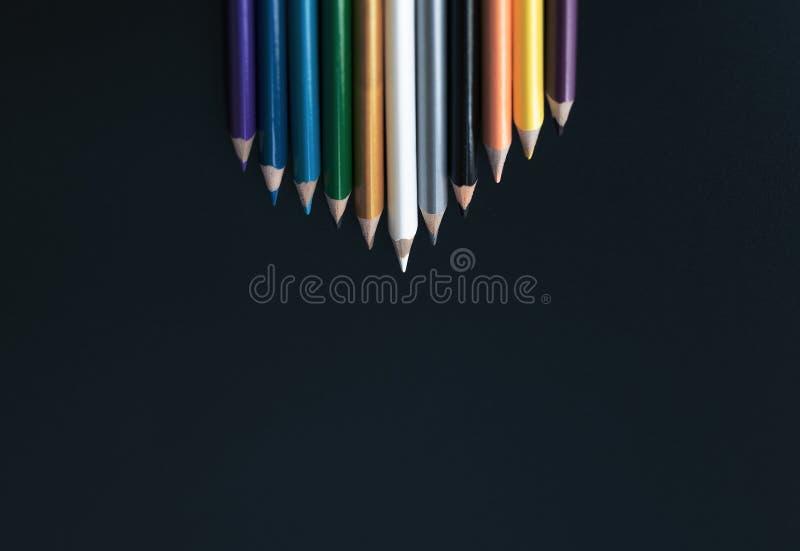 Leidings bedrijfsconcept het witte kleurenpotlood leidt andere kleur op zwarte achtergrond royalty-vrije stock afbeeldingen