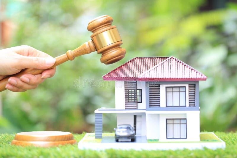 Leilão da propriedade, de mão da mulher casa de madeira e modelo do martelo da terra arrendada no fundo verde natural, advogado d foto de stock royalty free