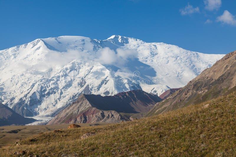 Leinin når en höjdpunkt, sikten från basläger 1, Pamir berg arkivbild