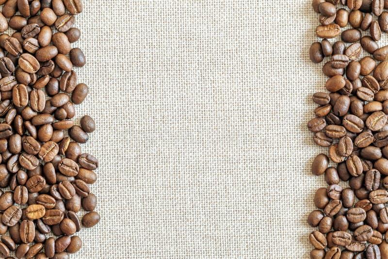 Leinwand-Sackleinen-Segeltuch und Kaffeebohnen setzten ringsum Foto zurück stockbild