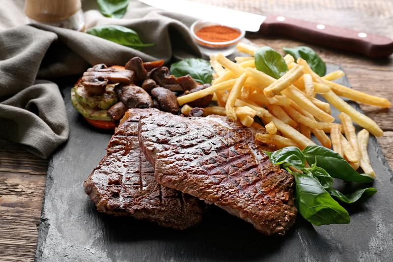 Leiplaat met heerlijke geroosterde lapjes vlees en frieten stock afbeeldingen