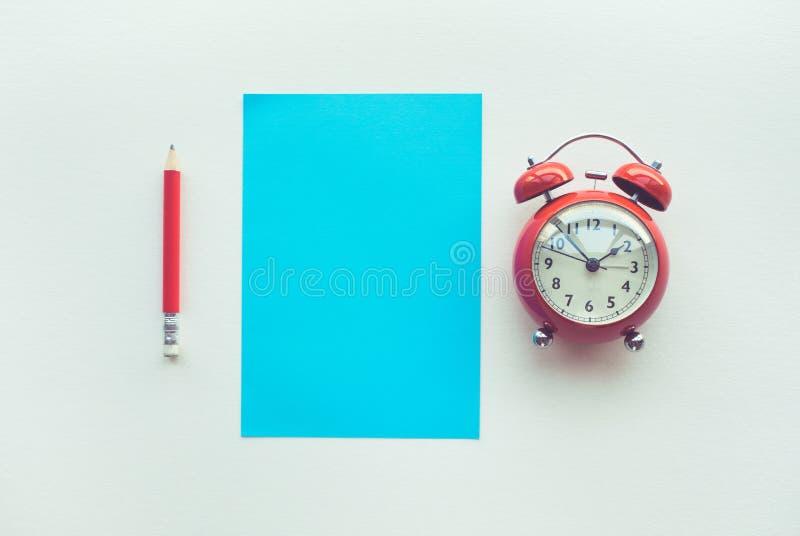 Leistungskonzepte mit Papier, Bleistift und Wecker auf Worktablehintergrund Zeit und Datumsgrenze lizenzfreies stockbild