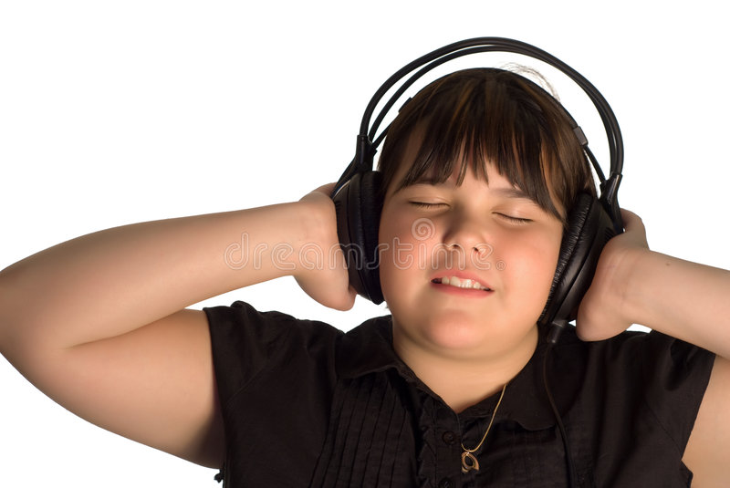 Leisure Activity. A young girl listening to some music on a large set of headphones stock photography