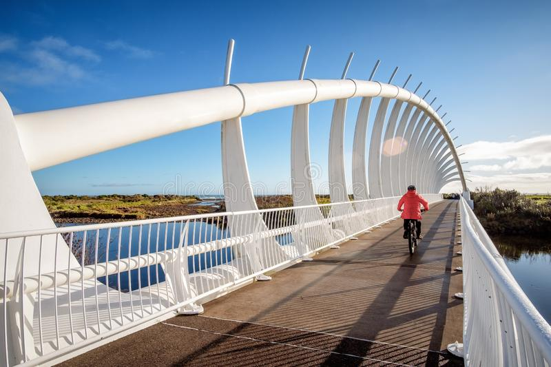 Leisure activity exercise image of a man biking across a bridge stock photo