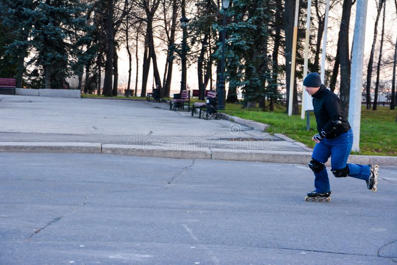 Leisure activity man roller skating in the central of the city on the sunset. Winter. stock photo
