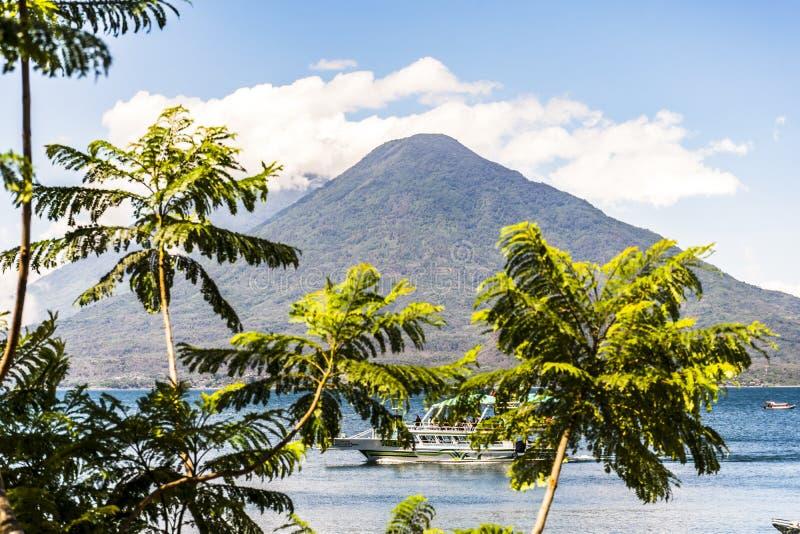 Leisure boat cruises on Lake Atitlan with 2 volcanoes behind, Guatemala royalty free stock image